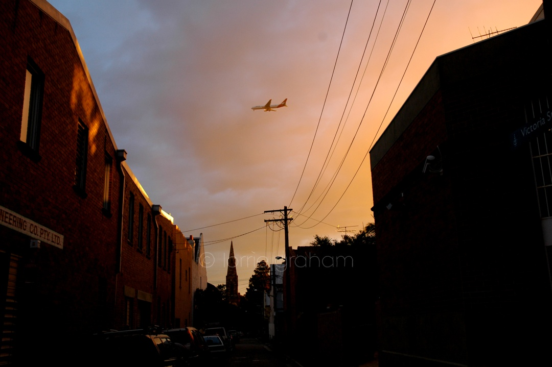 Lightbox - Plane in the sunset sky above Newtown